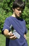 Telefone do menino e de pilha Fotos de Stock Royalty Free