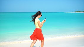 Telefone do uso da jovem mulher durante férias tropicais da praia Turista que usa o smartphone móvel filme