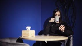 Telefone do uso da menina e para beber o café no café Mulher que usa o smartphone, consultando, lendo, conversando com amigos vídeos de arquivo