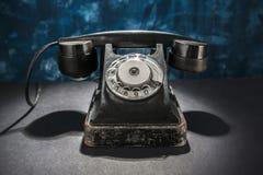 Telefone do vintage na obscuridade - fundo azul Fotos de Stock Royalty Free