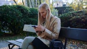 Telefone dos olhares e do toque da menina do sorriso, sentando-se em um banco no dia do outono video estoque