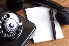 Telefone e bloco de notas pretos velhos foto de stock