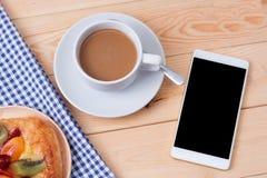 Telefone e xícara de café espertos no fundo de madeira Fotos de Stock Royalty Free