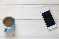 Telefone e xícara de café espertos no fundo de madeira Imagens de Stock Royalty Free
