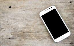 Telefone esperto branco no fundo de madeira, telefone celular branco fotografia de stock