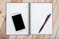 Telefone esperto, caderno na mesa Imagens de Stock