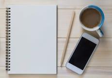 Telefone esperto com caderno e xícara de café e um lápis no fundo de madeira Fotografia de Stock