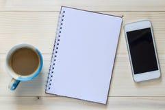 Telefone esperto com caderno e xícara de café no fundo de madeira Fotos de Stock
