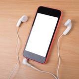 Telefone esperto com os fones de ouvido no modelo de superfície de madeira Imagem de Stock Royalty Free