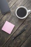 Telefone esperto com papel e a xícara de café pegajosos de nota Imagem de Stock Royalty Free