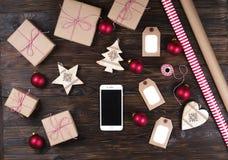 Telefone esperto com presentes de Natal na opinião superior do fundo de madeira Conceito em linha da compra do feriado Configuraç Fotografia de Stock