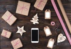 Telefone esperto com presentes de Natal na opinião superior do fundo de madeira Conceito em linha da compra do feriado Configuraç Imagens de Stock Royalty Free