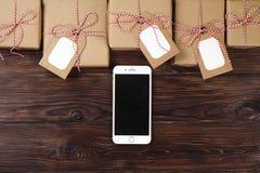Telefone esperto com presentes de Natal na opinião superior do fundo de madeira Conceito em linha da compra do feriado Configuraç Foto de Stock