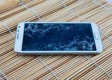 Telefone esperto com a tela quebrada no fundo de bambu Fotografia de Stock