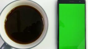 Telefone esperto com a tela verde ao lado do copo de café filme
