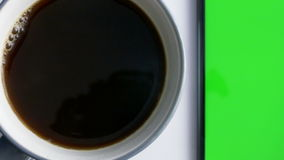 Telefone esperto com a tela verde ao lado do copo de café vídeos de arquivo