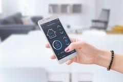 Telefone esperto da posse da mulher e controle home esperto app do uso a monitorar os parâmetros home imagem de stock