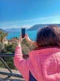 Telefone esperto de viagem do uso da mulher e toque de uma tela móvel na montanha e no mar foto de stock royalty free