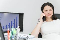Telefone esperto do uso atrativo da mulher de negócio e assento em seu wor Foto de Stock