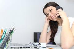 Telefone esperto do uso atrativo da mulher de negócio e assento em seu wor Fotos de Stock Royalty Free