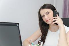 Telefone esperto do uso atrativo da mulher de negócio e assento em seu wor Fotografia de Stock Royalty Free