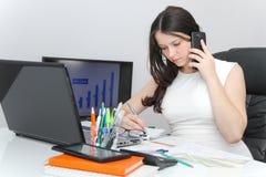 Telefone esperto do uso atrativo da mulher de negócio e assento em seu wor Foto de Stock Royalty Free