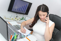 Telefone esperto do uso atrativo da mulher de negócio e assento em seu wor Imagens de Stock Royalty Free