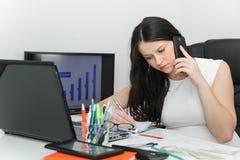 Telefone esperto do uso atrativo da mulher de negócio e assento em seu wor Imagem de Stock