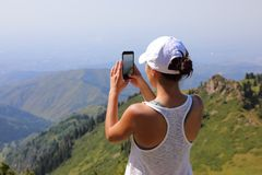 Telefone esperto do uso da mulher que toma a foto foto de stock royalty free