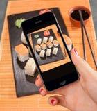 Telefone esperto na mão das mulheres para tomar a foto do sushi Fotos de Stock Royalty Free