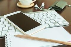 Telefone esperto no teclado e no bloco de notas com lápis Fotografia de Stock Royalty Free