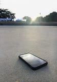 Telefone esperto que encontra-se em uma areia da praia clara com como luz do por do sol, é social médio da parada para relaxa Imagem de Stock