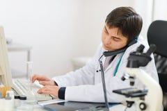 Telefone falador médico ocupado e trabalho no PC Fotografia de Stock