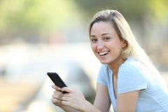 Telefone feliz da terra arrendada do adolescente que olha a câmera fotos de stock