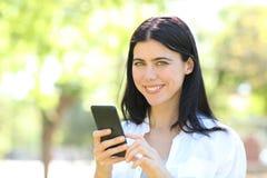 Telefone feliz da terra arrendada da mulher adulta que olha a câmera foto de stock royalty free