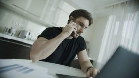 Telefone irritado da chamada do homem na cozinha Telefone celular de fala da pessoa frustrante video estoque