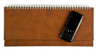 Telefone móvel em um caderno Imagem de Stock