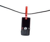 Telefone móvel em uma linha de roupa Fotografia de Stock Royalty Free