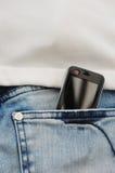 Telefone móvel nas calças de brim Fotografia de Stock