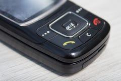 Telefone móvel velho Uma chave com um monofone verde no primeiro plano fotografia de stock royalty free