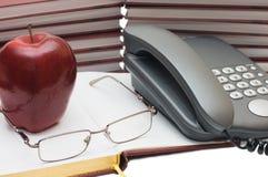 Telefone, maçã e vidros no livro Fotografia de Stock