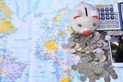 telefone, mealheiro, moeda esperta da pilha e calculadora postos sobre o mundo Imagens de Stock Royalty Free