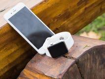 Telefone moderno e um relógio Fotos de Stock Royalty Free