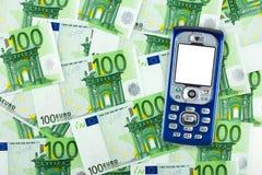 Telefone móvel no fundo do dinheiro Imagens de Stock