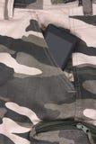 Telefone no bolso do short/calças da camuflagem Fotos de Stock