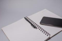 Telefone, pena e caderno espertos na tabela do escritório no fundo branco Conceito do orçamento Fotografia de Stock Royalty Free