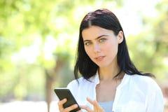Telefone sério da terra arrendada da mulher adulta que olha a câmera foto de stock royalty free