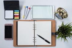 Telefone, tabuleta digital, pulso de disparo, planta, almofada de memorando e anule o caderno com em configuração branca do plano Foto de Stock