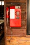 Telefone vermelho velho em uma parede de madeira fotos de stock