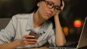 Telefoneert de uiterst vermoeide dame die freelancer en op laptop, geen energie liggen scrollen stock videobeelden